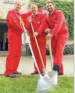 Günter Freitag, Bernhard Hadel und Guido van den Berg posieren beim Pressetermin in Arbeitskluft und Gartengeräten vor dem Fritz-Erler-Haus in Liblar