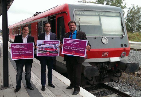 Sascha Solbach, Dierk Timm und Guido van den Berg MdL mit Plakaten der SPD-S-Bahn Kampagne auf dem Bedburger Bahnhof (2014)