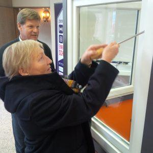 Bürgerin testet Einbruchsschutz an einem Fenster