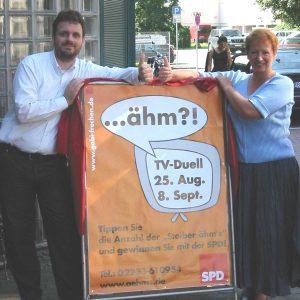 Gabi Frechen und Guido van den Berg präsentieren das Ähm-Plakat.