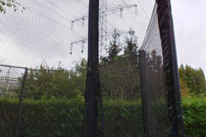 Blick aus einem Garten zur driekt daneben verlaufenden Ultranetleitung durch das Netz eines Trampolins