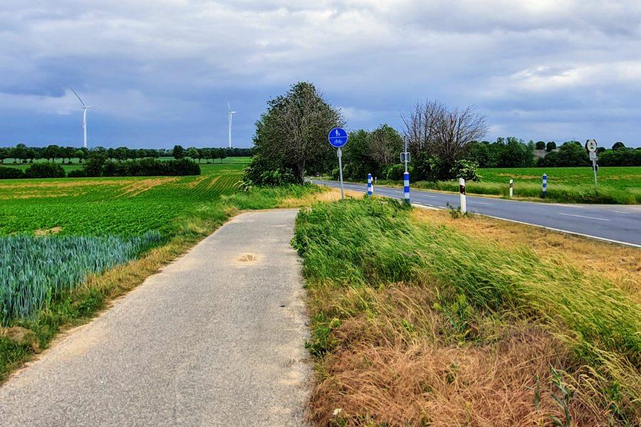 Kurzes Radwegfragment unter stürmischem Himmel an der K38