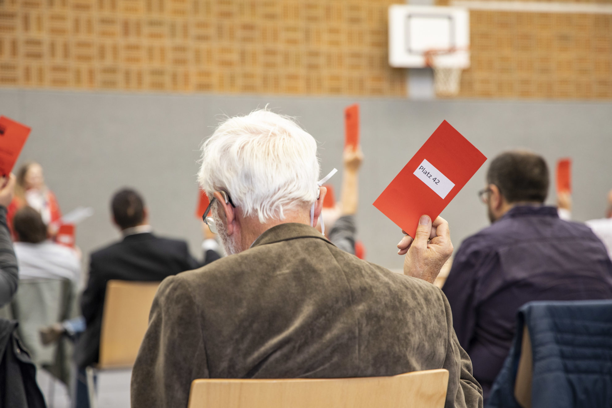 Ansicht von hintern: sitzendes PArteimitglied mit Wahlkarte