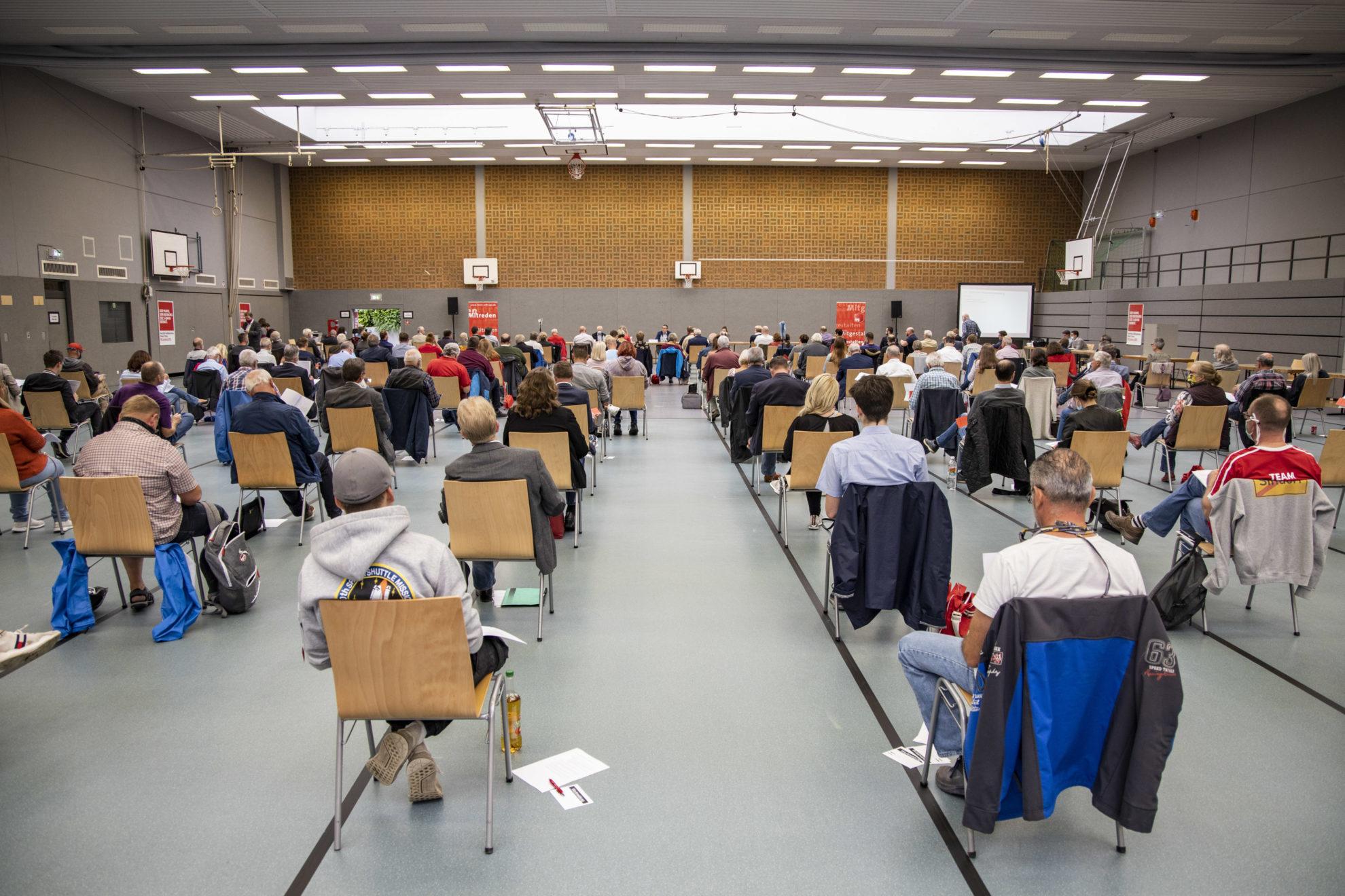 Ansicht der gefüllten Turnhalle in Richtung Sitzungsleitung, alle auf Abstand