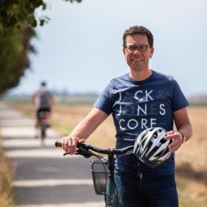 Dierkt Timm steht mit seinem Fahrrad und einem Helm in der Hand auf einem schattigen, breiten Radweg