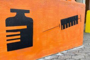 Impfzentrum Hürth Darstellung Spritze und Viole auf Betonblock vor Gebäude