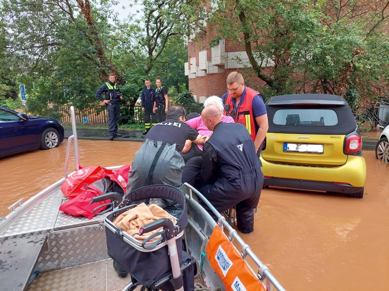 Fluthelfer von DLRG und Feuerwehr heben eine ältere Dame in ein Rettungsboot in einer überfluteten Straße